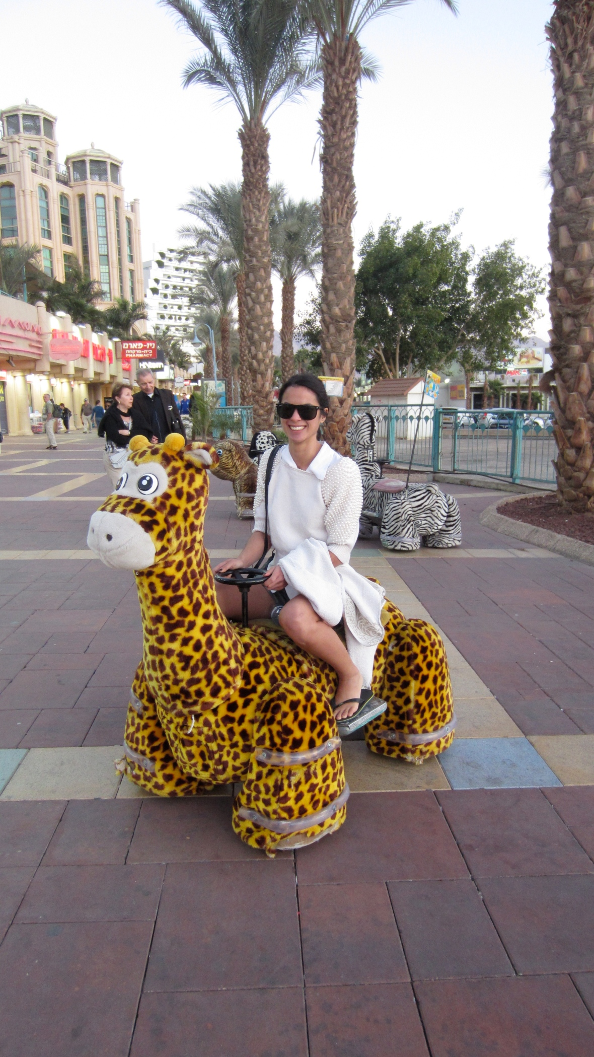 Sitting on a toy giraffe in Eilat, Israel